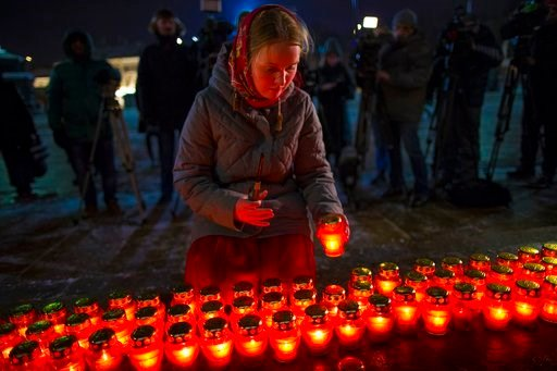 (AP Photo/Alexander Zemlianichenko). A girl places a candle as a group gather at the Cathedral of Christ the Savior in Moscow to light 71 candles in memory of those killed in the An-148 plane crash, on Monday, Feb. 12, 2018.  A Russian passenger plane ...