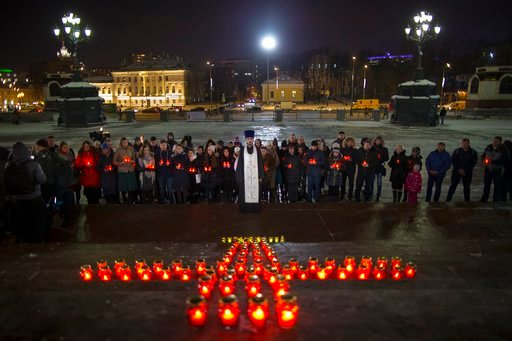 (AP Photo/Alexander Zemlianichenko). Orthodox youth with a priest gather at the Cathedral of Christ the Savior in Moscow lighting 71 candles in memory of those killed in the An-148 plane crash, Monday, Feb. 12, 2018. A Russian passenger plane carrying ...