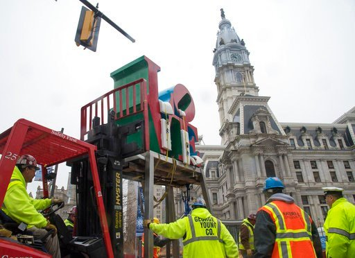(Clem Murray/The Philadelphia Inquirer via AP, File). FILE - In this Feb. 23, 2016, file photo, workers temporarily relocate artist Robert Indiana's LOVE sculpture before the start of renovations to its traditional location in John F. Kennedy Plaza, al...