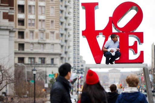 (AP Photo/Matt Rourke, File). FILE - In this March 27, 2015, file photo, a young man climbs on artist Robert Indiana's LOVE sculpture in John F. Kennedy Plaza, also known as Love Park, in Philadelphia. The sculpture, temporarily relocated in 2016 befor...