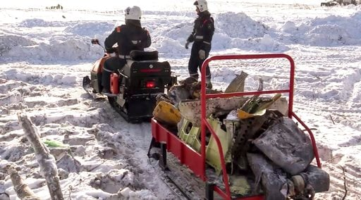 (Russian Ministry for Emergency Situations photo via AP). In this photo provided by the Russian Emergency Situations Ministry, emergency personnel carry wreckage of an AN-148 plane crash in Stepanovskoye village, about 40 kilometers (25 miles) from the...
