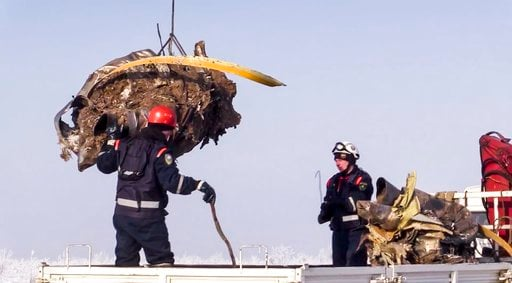 (Russian Ministry for Emergency Situations photo via AP). In this photo provided by the Russian Emergency Situations Ministry, emergency personnel load debris of an engine of the AN-148 plane crash on a truck in Stepanovskoye village, about 40 kilomete...