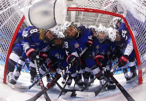 (Bruce Bennett/Pool Photo via AP). Players from the United States pose for the camera as they gather around the goal before the preliminary round of the women's hockey game against the team from Russia at the 2018 Winter Olympics in Gangneung, South Ko...