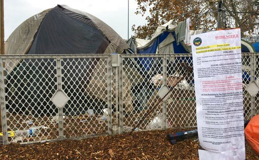 (AP Photo/Amy Taxin, File). FILE - In this Jan. 8, 2018 file photo, signs warning homeless residents they'll need to move out of a two-mile long encampment are posted in Anaheim, Calif. A long-running dispute over a Southern California county's plans t...