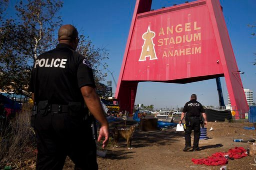 (AP Photo/Jae C. Hong, File). FILE - In this Dec. 19, 2017, file photo, two police officers, Eric Meier, right, and Curtis Bynum from the Anaheim Police Department's homeless outreach team walk through a homeless encampment set up outside Angel Stadium...