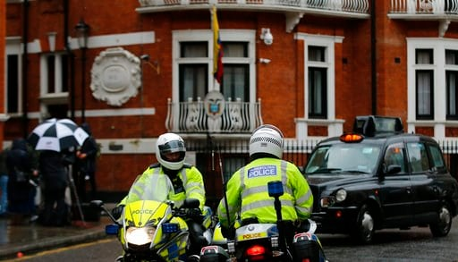 (AP Photo/Alastair Grant). Police motorcyclists briefly stop outside the Ecuadorian embassy in London, Tuesday, Feb. 13, 2018. A British judge is set to decide Tuesday whether to quash or uphold an arrest warrant for WikiLeaks founder Julian Assange, w...