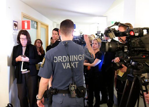 ( Janerik Henriksson/ TT via AP). A security guard and journalists gather outside a court room in Stockholm Tuesday February 13, 2018. The trial has started of an Uzbek man Rakhmat Akilov who has confessed to ramming a stolen truck into a crowd in down...