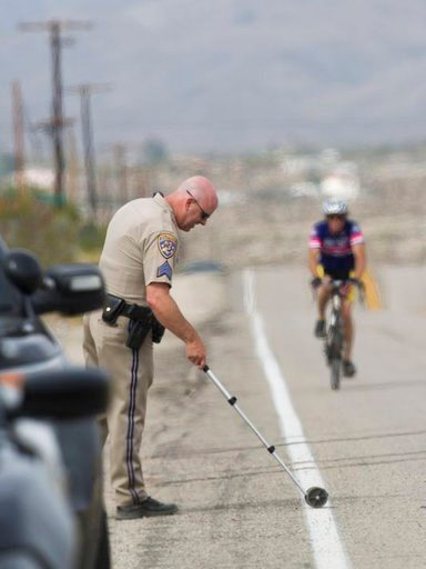 (Omar Ornelas/The Desert Sun via AP ). California Highway Patrol investigator takes measurements at the scene where a vehicle struck two cyclists participating in the 2018 Tour de Palm Springs near Indio Hills, Calif., Saturday, Feb. 10, 2018. Police s...