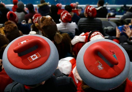 (AP Photo/Aaron Favila). Spectators sport headwear shaped as curling stones as they watch the mixed doubles curling finals match against Canada and Switzerland at the 2018 Winter Olympics in Gangneung, South Korea, Tuesday, Feb. 13, 2018.