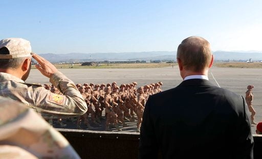 (Mikhail Klimentyev/Pool Photo via AP, File). FILE - In this file photo taken on Tuesday, Dec. 12, 2017, Russian President Vladimir Putin, right, watches the troops marching as he and Syrian President Bashar Assad visit the Hemeimeem air base in Syria....