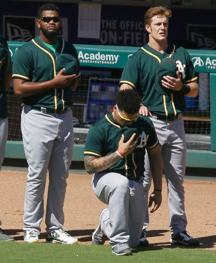 (AP Photo/LM Otero, File). FILE - In this Sunday, Oct. 1, 2017 file photo, Oakland Athletics catcher Bruce Maxwell takes a knee during the national anthem next to teammates Mark Canha, right, and Raul Alcantara before a baseball game against the Texas ...