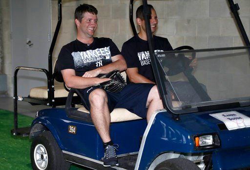 (AP Photo/Lynne Sladky). New York Yankees relief pitcher Adam Warren, left, rides in a golf cart at baseball spring training, Tuesday, Feb. 13, 2018, in Tampa, Fla.