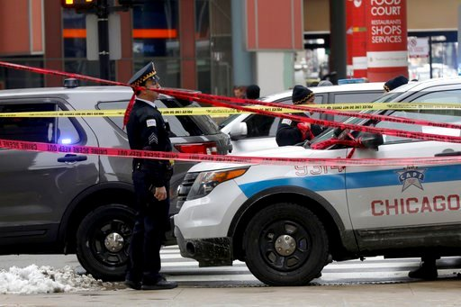 (John J. Kim/Chicago Tribune via AP). Police guard the scene where an off-duty officer was shot while assisting a tactical team at a state government office building, Tuesday, Feb. 13, 2018, in Chicago.