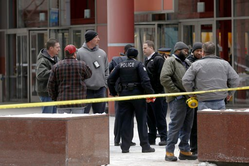 (John J. Kim / Chicago Tribune)/Chicago Tribune via AP). Police guard the crime scene after an off-duty Chicago police officer was shot at the James R. Thompson Center, Feb. 13, 2018.