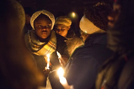 (Casey Sykes /The Grand Rapids Press via AP). Dozens of people braved the freezing temperature to gather together and hold a vigil for Mujey Dumbuya, 16, at her bus stop across the street from the Chicken Coop on Eastern Ave SE in Grand Rapids, Michiga...