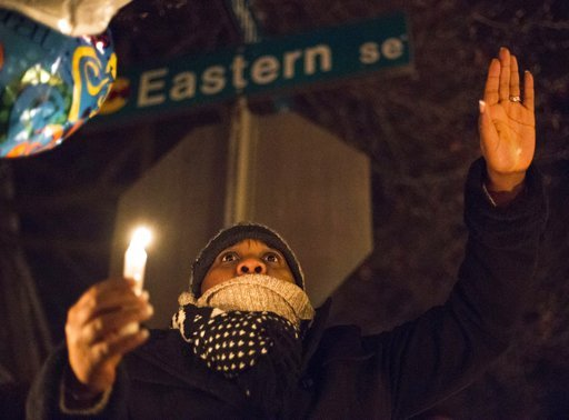 "(Casey Sykes /The Grand Rapids Press via AP). A person sings the Christian hymn ""It Is Well"" as dozens of people brave the freezing temperature to gather together and hold a vigil for Mujey Dumbuya, 16, at her bus stop across the street from the Chicke..."