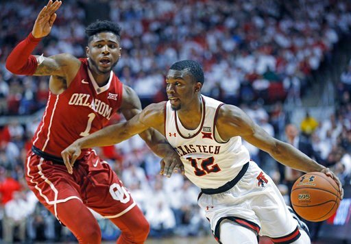 (AP Photo/Brad Tollefson). Texas Tech's Keenan Evans (12) lays up the ball around Oklahoma's Christian James (1) during an NCAA college basketball game Tuesday, Feb. 13, 2018, in Lubbock, Texas.