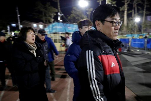 (AP Photo/Julio Cortez). In a photo taken Monday, Feb. 12, 2018, Kim Woo Il, right, walks with his wife Heo Saeng-gum, left, and their son Kim Se Hyung, center, as arrive at the Kwandong Hockey Center to watch their daughter Kim Selin play for the Kore...