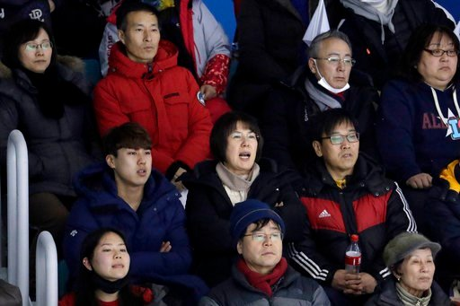 (AP Photo/Julio Cortez). In a photo taken Monday, Feb. 12, 2018, Heo Saeng-gum, center, mother of South Korean player Kim Selin, reacts while sitting with her son Kim Se Hyung, left, and her husband Kim Woo Il, right, as they watch Kim Selin play for t...