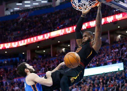 (AP Photo/Sue Ogrocki). Cleveland Cavaliers forward LeBron James hangs from the basket after dunking in front of Oklahoma City Thunder guard Alex Abrines during the first half of an NBA basketball game in Oklahoma City, Tuesday, Feb. 13, 2018.