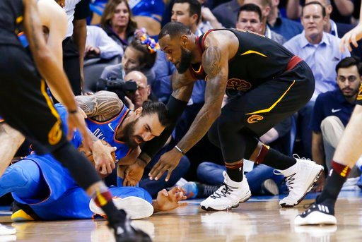 (AP Photo/Sue Ogrocki). Cleveland Cavaliers forward LeBron James, right, reaches in for the ball held by Oklahoma City Thunder center Steven Adams during the first half of an NBA basketball game in Oklahoma City, Tuesday, Feb. 13, 2018.