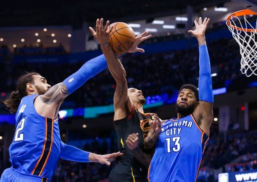 (AP Photo/Sue Ogrocki). Oklahoma City Thunder center Steven Adams, left, knocks the ball away from Cleveland Cavaliers guard George Hill, center, as Hill shoots in front of forward Paul George (13) during the first half of an NBA basketball game in Okl...