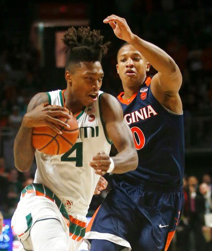 (AP Photo/Wilfredo Lee). Miami guard Lonnie Walker IV (4) drives to the basket against Virginia guard Devon Hall (0) during the first half of an NCAA college basketball game, Tuesday, Feb. 13, 2018, in Coral Gables, Fla.