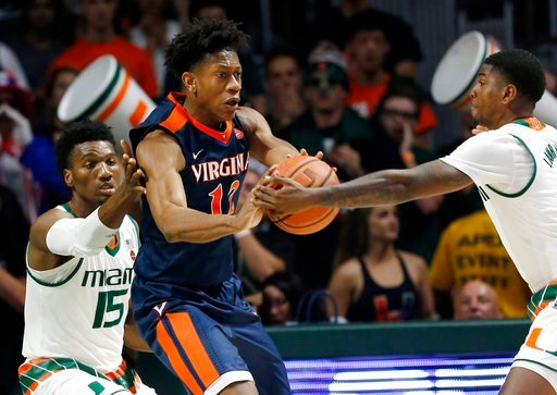 (AP Photo/Wilfredo Lee). Miami guard Anthony Lawrence II, right, steals the ball from Virginia guard De'Andre Hunter (12) as center Ebuka Izundu (15) guards from behind during the first half of an NCAA college basketball game, Tuesday, Feb. 13, 2018, i...