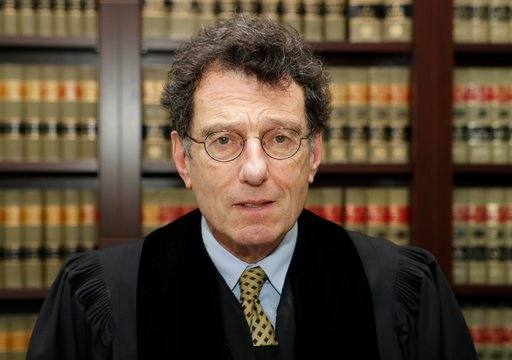 "(AP Photo/Tony Dejak, file). FILE - This Jan. 11, 2018 file photo shows judge Dan Polster in his office in Cleveland. Polster has called the opioid addiction epidemic ""100 percent man-made"" and asserted that other branches of government have ""punted"" o..."
