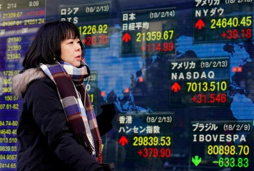 (AP Photo/Shizuo Kambayashi). A woman walks past an electronic stock indicator of a securities firm in Tokyo, Wednesday, Feb. 14, 2018. Asian shares were mixed Wednesday amid a wait-and-see mood ahead of Lunar New Year holidays as well as the release o...