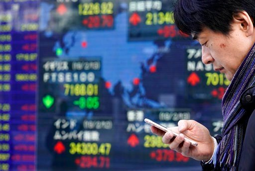 (AP Photo/Shizuo Kambayashi). A man uses a smartphone in front of an electronic stock indicator of a securities firm in Tokyo, Wednesday, Feb. 14, 2018. Asian shares were mixed Wednesday amid a wait-and-see mood ahead of Lunar New Year holidays as well...