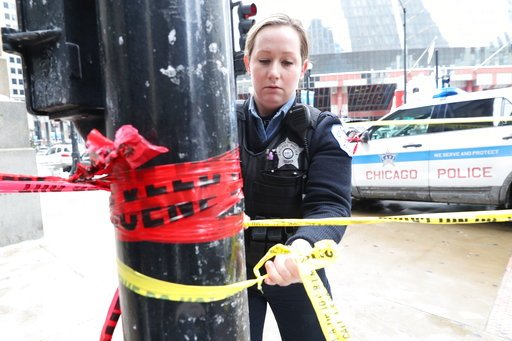 (John J. Kim/Chicago Tribune via AP). A Chicago police officer strings crime scene tape across from the Thompson Center after an off-duty officer was shot in Chicago, Tuesday, Feb. 13, 2018.