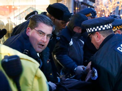 (AP Photo/Charles Rex Arbogast). In this Feb. 23, 2016, photo, then Chicago police Capt. Paul Bauer, left, takes part in the arrest of a protester outside an Apple store on Magnificent Mile in Chicago.