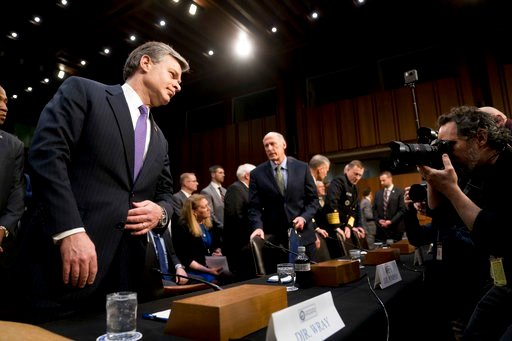 (AP Photo/Andrew Harnik). FBI Director Christopher Wray, left, and Director of National Intelligence Dan Coats, center, arrive for a Senate Select Committee on Intelligence hearing on worldwide threats, Tuesday, Feb. 13, 2018, in Washington.