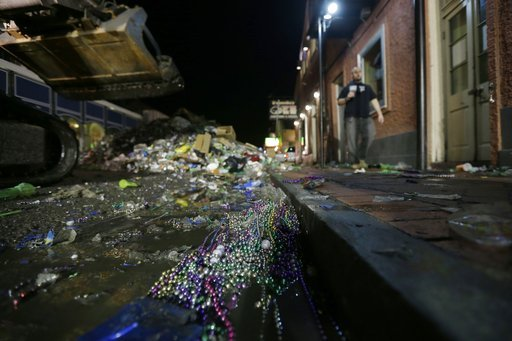(AP Photo/Gerald Herbert). FILE - In this Feb. 13, 2013 file photo, people walk past debris debris on Bourbon Street in the early morning of Ash Wednesday, the day after Mardi Gras, in the French Quarter of New Orleans. Mardi Gras produces fun-filled d...