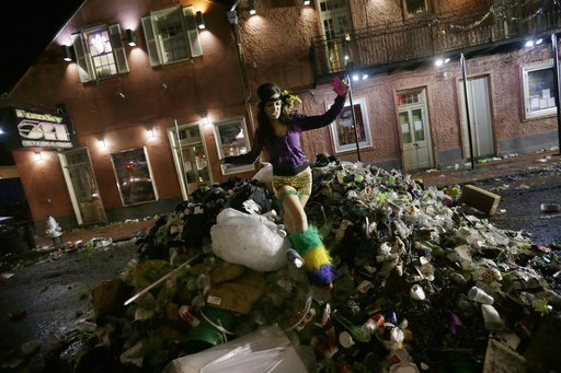 (AP Photo/Gerald Herbert, File). FILE - In this Feb. 13, 2013 file photo, Melissa, no last name given, a VIP hostess and bartender at a Bourbon Street club, jumps on a pile of debris as she walk home with co-workers on Bourbon Street in the early morni...