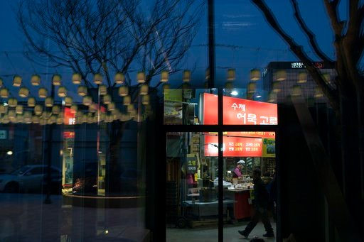 (AP Photo/Felipe Dana). Decorative lamps are reflected on a glass door as a man walks past a restaurant at the traditional market in Gangneung, South Korea, Tuesday, Feb. 13, 2018. Markets in South Korea can range in size from simple gatherings held ev...