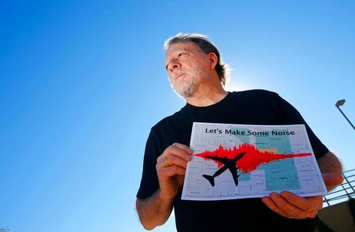 (AP Photo/Ross D. Franklin, File). FILE - In this Feb. 6, 2015 file photo, Steve Dreiseszun, a resident of the F.Q. Story historic district in Phoenix, holds a graphic of the increased noise brought on by airplanes flying along new flight paths out of ...