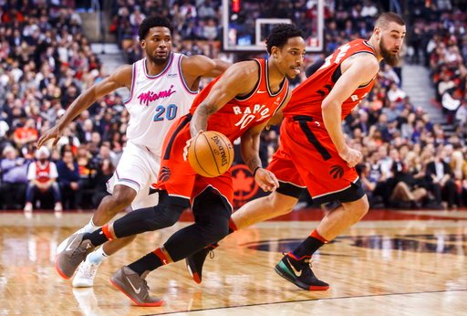 (Mark Blinch/The Canadian Press via AP). Toronto Raptors DeMar DeRozan goes to the basket with teammate Jonas Valanciunas, right, against Miami Heat Justise Winslow, left, during the first half of an NBA basketball game, Tuesday, Feb. 13, 2018, in Toro...
