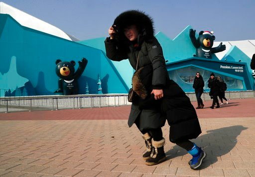 (AP Photo/Julie Jacobson). A woman shields her face and a child from gusty winds that whipped through Gangneung Olympic Park at the 2018 Winter Olympics in Gangneung, South Korea, Wednesday, Feb. 14, 2018. Spectators were advised to either stay inside ...