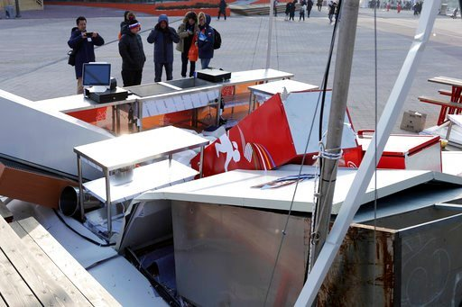 (AP Photo/Julio Cortez). People look at a concession stand blown by gusty winds at the Olympic Park at the 2018 Winter Olympics in Gangneung, South Korea, Wednesday, Feb. 14, 2018. Gusts forced organizers to shut down the common areas in Olympic Park a...
