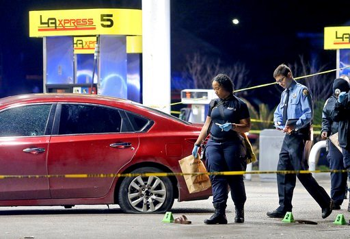 (Michael DeMocker/NOLA.com The Times-Picayune via AP). Crime scene technicians gather evidence next to a bullet-riddled red Nissan sedan with a homicide victim inside as New Orleans Police investigate after several people were shot, in the lower Ninth ...
