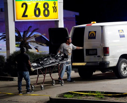 (AP Photo/Gerald Herbert). Police move a body into a coroner van at the scene of a Mardi Gras day shooting that left at least one dead and others injured, in the lower ninth ward in New Orleans, Tuesday, Feb. 13, 2018.