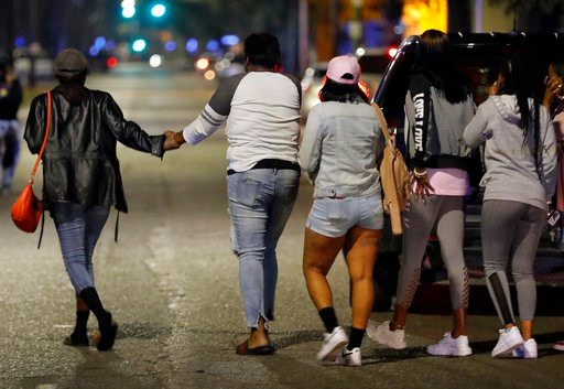 (AP Photo/Gerald Herbert). A woman is led away from the scene as police investigate the scene of a Mardi Gras day shooting that left at least one dead and others injured, in the lower ninth ward in New Orleans, Tuesday, Feb. 13, 2018.