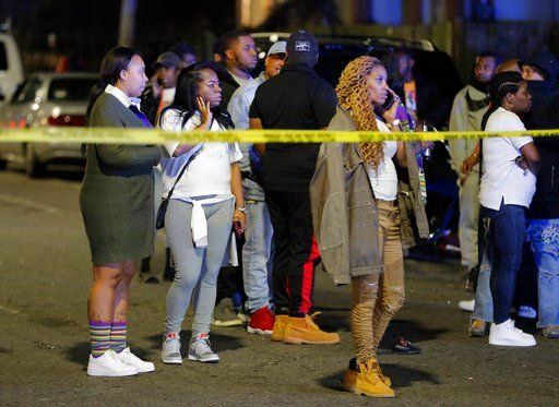 (AP Photo/Gerald Herbert). Onlookers watch as police investigate the scene of a Mardi Gras day shooting in the lower Ninth Ward in New Orleans, Tuesday, Feb. 13, 2018.