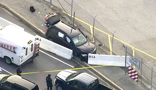 (WUSA TV-9 via AP). In this image made from video and provided by WUSA TV-9, authorities investigate the scene of a shooting at Fort Meade, Md. on Wednesday, Feb. 14, 2018. A suspect has been held, taken from the black SUV that stopped at barrier after...