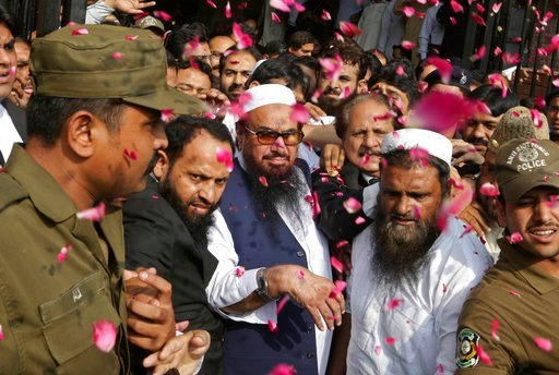 (AP Photo/K.M. Chaudary). FILE - In this Thursday, Oct. 19, 2017 file photo, supporters of Hafiz Saeed, center, head of the Pakistani religious party, Jamaat-ud-Dawa, is showered with rose petals by his supporters as he arrives to a court in Lahore, Pa...