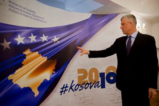 (AP Photo/Visar Kryeziu). Kosovo President Hashim Thaci points toward a banner marking the 10th anniversary of Kosovo independence during an interview with The Associated Press on Wednesday Feb. 14, 2018, in Kosovo capital Pristina. Hashim Thaci said 2...