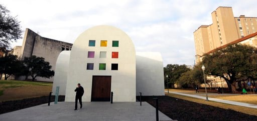 """(AP Photo/Eric Gay). In this Monday, Feb. 12, 2018, photo, a man passes Ellsworth Kelly's """"Austin"""" at the Blanton Museum of Art, in Austin, Texas. The exhibit, a 2,715-square-foot stone building with luminous colored glass windows is set to open to the..."""