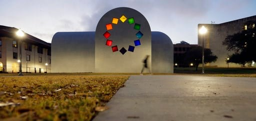 """(AP Photo/Eric Gay). In this Monday, Feb. 12, 2018, photo, a woman passes Ellsworth Kelly's """"Austin"""" at the Blanton Museum of Art, in Austin, Texas. The exhibit, a 2,715-square-foot stone building with luminous colored glass windows is set to open to t..."""